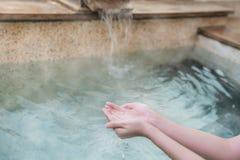 Cucharada de la fianza de la chica joven del agua de las aguas termales imagenes de archivo