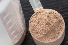 Cucharada de la proteína del aislante del suero del chocolate delante de la coctelera de la proteína y de sus piezas Fotografía de archivo libre de regalías