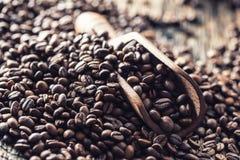 Cucharada de madera por completo de los granos de café en la tabla de roble vieja fotografía de archivo