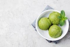 Cucharada del helado del matcha del té verde en el cuenco blanco en un fondo de piedra gris Copie la opinión superior del espacio Fotos de archivo