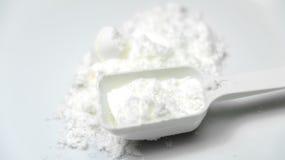 Cucharada del polvo amino de la proteína del colágeno blanco con la cuchara aislada Fotografía de archivo
