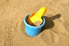 Cucharada y compartimiento en la arena Fotografía de archivo