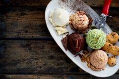 Cucharadas de los sabores clasificados del helado en el disco Imagen de archivo libre de regalías