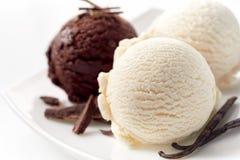 Cucharadas del chocolate y de la crema de Vanilla Ice en la placa Fotografía de archivo