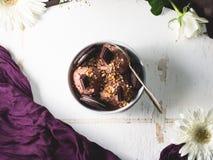 Cucharadas del helado de chocolate en cuenco en la tabla blanca Foto de archivo libre de regalías