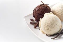 Cucharadas del helado de la vainilla y de chocolate en la placa Fotografía de archivo
