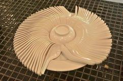 Cucharas blancas espirales alrededor de una taza en la placa Fotos de archivo libres de regalías