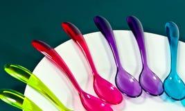 Cucharas coloridas en la placa blanca Foto de archivo libre de regalías