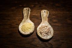 Cucharas de cerámica con la harina de avena y el maíz en una tabla de madera estilizado Fotos de archivo