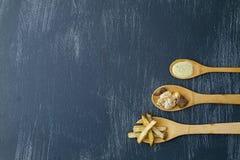 Cucharas de madera con los ingredientes para preparar la carne con las patatas y el cilantro foto de archivo libre de regalías