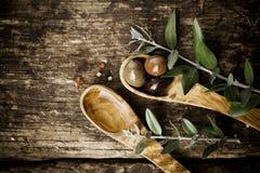 Cucharas de madera verdes olivas con las aceitunas frescas Imagen de archivo libre de regalías