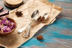 Cucharas del té del vintage y pétalos color de rosa en fondo azul de madera Foto de archivo libre de regalías