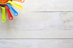 Cucharas dosificadoras coloridas para la cocina en un backgrou de madera blanco Imágenes de archivo libres de regalías