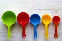 Cucharas dosificadoras coloridas para la cocina en un backgrou de madera blanco Imagen de archivo