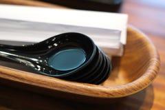 Cucharas negras en caja de madera Fotografía de archivo