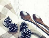Cucharas y conos de madera del pino en una vieja superficie de madera blanca Imagen de archivo
