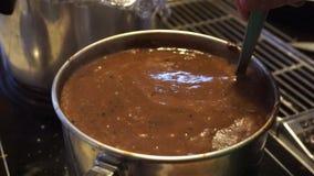 Cucharee el revolvimiento de la salsa marrón en stovetop almacen de metraje de vídeo