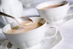 Cucharilla sobre la taza de té o de co Fotografía de archivo