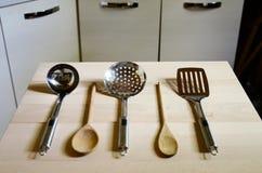 Cucharones en la tabla de madera en fondo de la cocina Imagen de archivo
