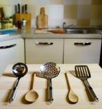 Cucharones en la tabla de madera en fondo de la cocina Imagen de archivo libre de regalías