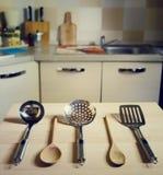 Cucharones en la tabla de madera en fondo de la cocina Imágenes de archivo libres de regalías