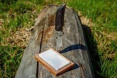 Cuchillo afilado y muela en un fondo de madera imagenes de archivo