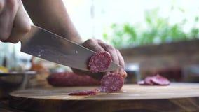 Cuchillo ascendente cercano en las manos masculinas que cortan el salami de la salchicha en la tabla de madera Cortes del cociner almacen de video