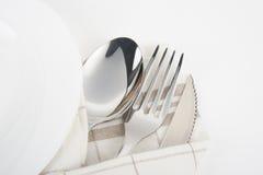 Cuchillo, bifurcación y cuchara con la servilleta de lino Imagen de archivo