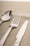 Cuchillo, bifurcación y cuchara con la servilleta de lino Fotografía de archivo