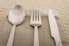 Cuchillo, bifurcación y cuchara con la servilleta de lino Fotos de archivo