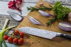 Cuchillo con la comida sana - verduras, cebolla, ensalada, tomates, patata colocada en una tabla de cortar con la opinión superio imagen de archivo