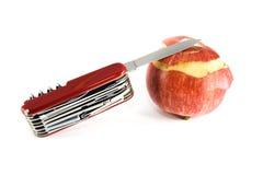 Cuchillo de bolsillo y manzana parcialmente pelada Imagen de archivo libre de regalías