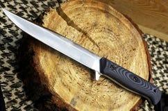 Cuchillo de caza en un soporte de madera Imagenes de archivo