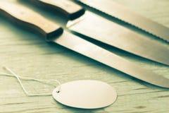 Cuchillo de cocina con una etiqueta en fondo de madera Imágenes de archivo libres de regalías