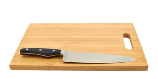 Cuchillo de cocina de acero en tabla de cortar Imagenes de archivo