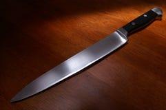 Cuchillo de cocina en la tabla Foto de archivo libre de regalías