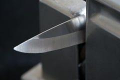 Cuchillo de cocina en una herramienta afiladora Fotografía de archivo