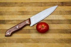 Cuchillo de cocina en una tarjeta de corte fotos de archivo
