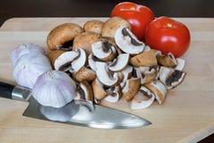 Cuchillo de cocina de los clavos de ajo de los tomates de las setas en tabla de cortar Fotografía de archivo libre de regalías