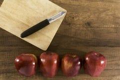 Cuchillo de pelado en la tabla de cortar con las manzanas Imágenes de archivo libres de regalías