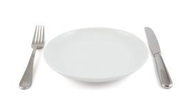 Cuchillo de tabla, bifurcación y placa de cerámica aislados Imágenes de archivo libres de regalías