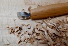 Cuchillo de talla en un cuenco de madera con las virutas Fotografía de archivo libre de regalías