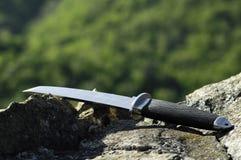 Cuchillo de Tanto en roca Fotos de archivo