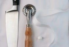 Cuchillo del cocinero, cortador de los pasteles y uniforme Imágenes de archivo libres de regalías