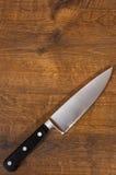 Cuchillo del cocinero de la cocina en el fondo de madera marrón de la tabla Con el espacio de la copia Visión superior Imágenes de archivo libres de regalías