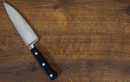 Cuchillo del cocinero de la cocina en el fondo de madera marrón de la tabla Con el espacio de la copia Visión superior Fotos de archivo libres de regalías