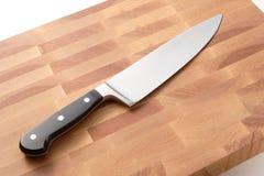 Cuchillo del cocinero en la tarjeta de corte de madera fotos de archivo libres de regalías