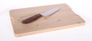 Cuchillo en la tarjeta de corte Imagenes de archivo