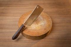 Cuchillo en un carnicero de madera en fondo de madera Foto de archivo