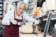 Cuchillo feliz de Slicing Cheese With del vendedor en tienda imágenes de archivo libres de regalías